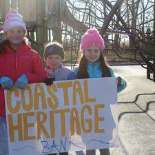 Kids holding a Coastal Heritage Bank sign