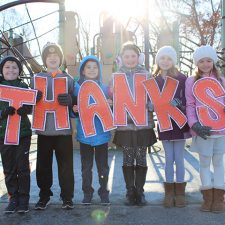 """Kids holding up a """"THANKS"""" sign"""